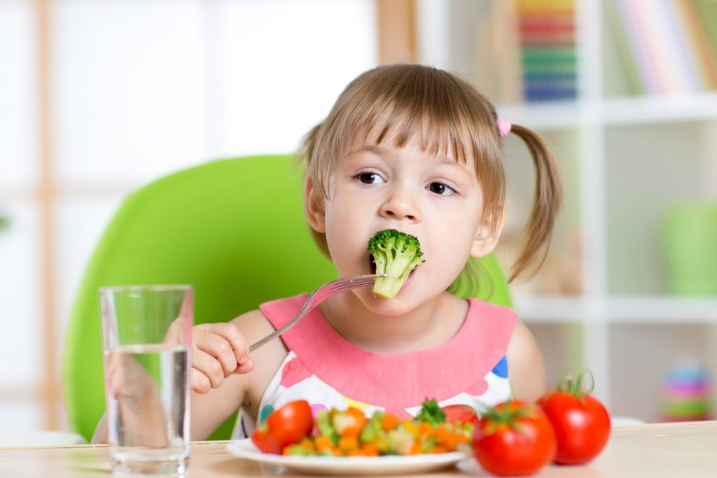 Little girl eating her vegetables