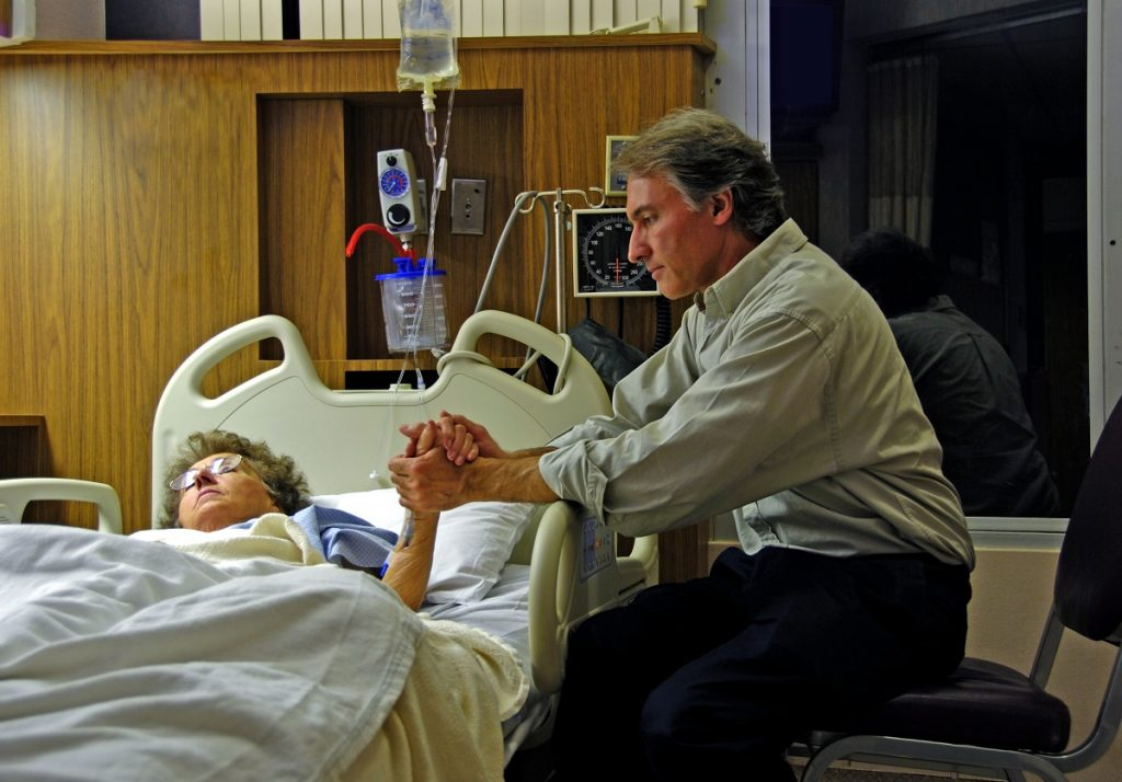 man holding his wife's hand in a hospital