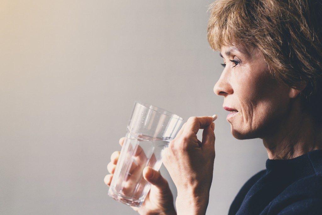 woman drinking medicine