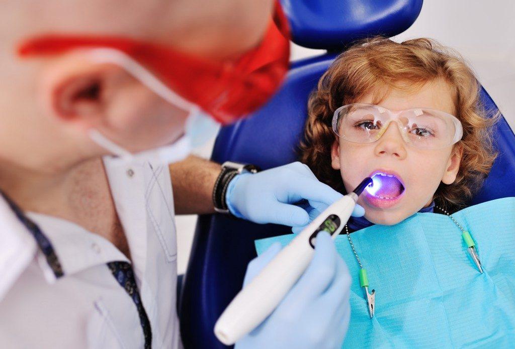 dentist cleaning kid's teeth
