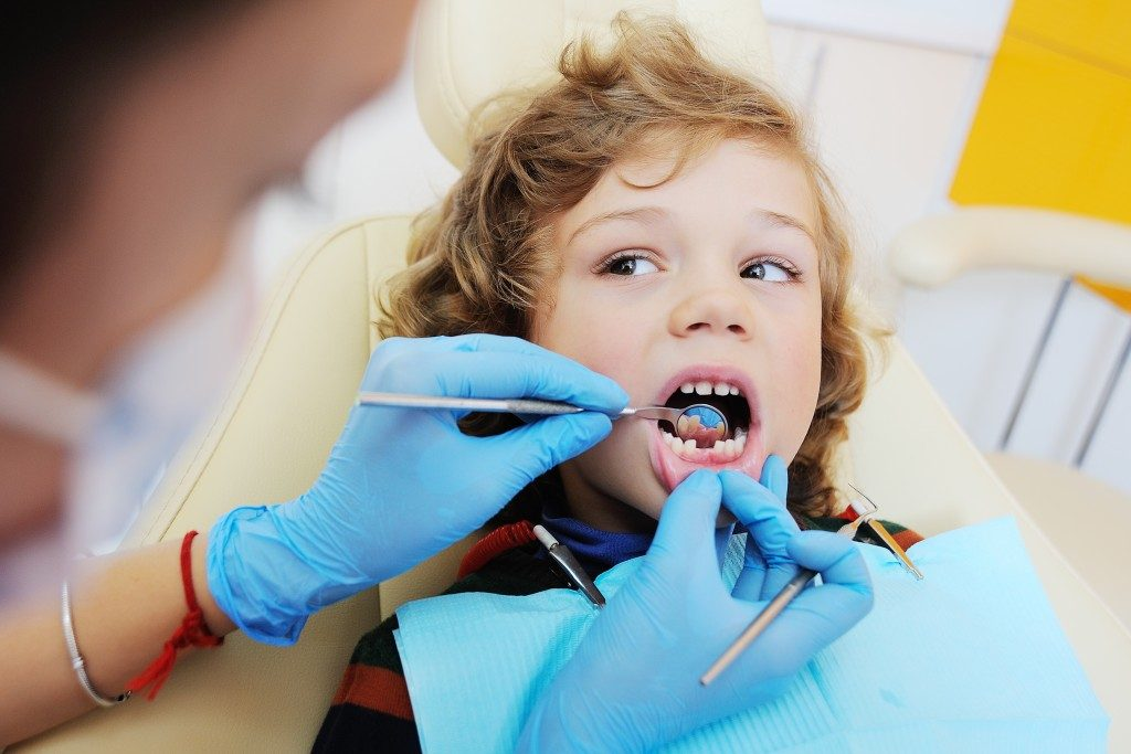 kid getting his tooth checked by dentist