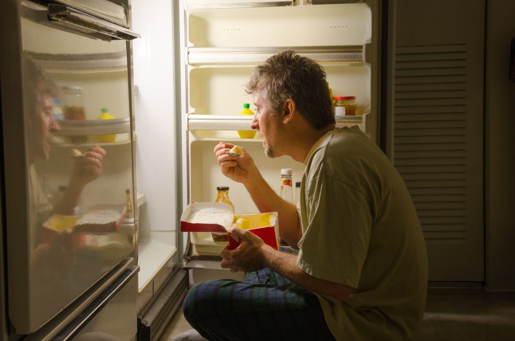 man eating straight out of the fridge