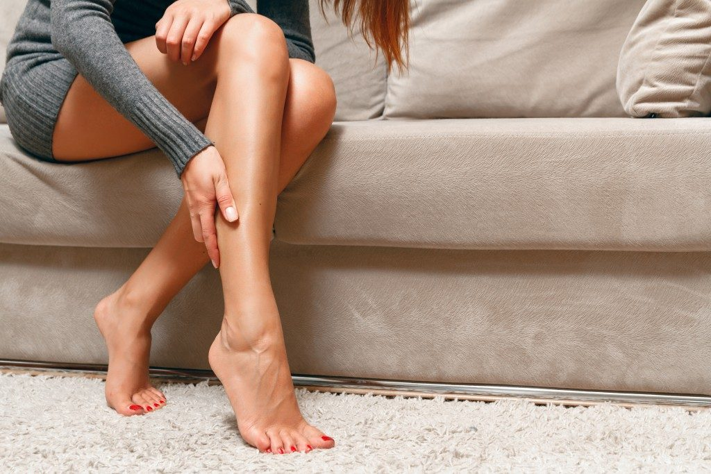 woman sitting in the couch, suffering pain in her feet