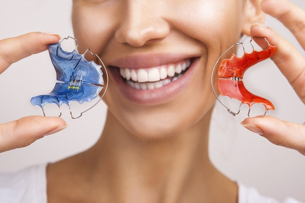 Woman holding dental retainers