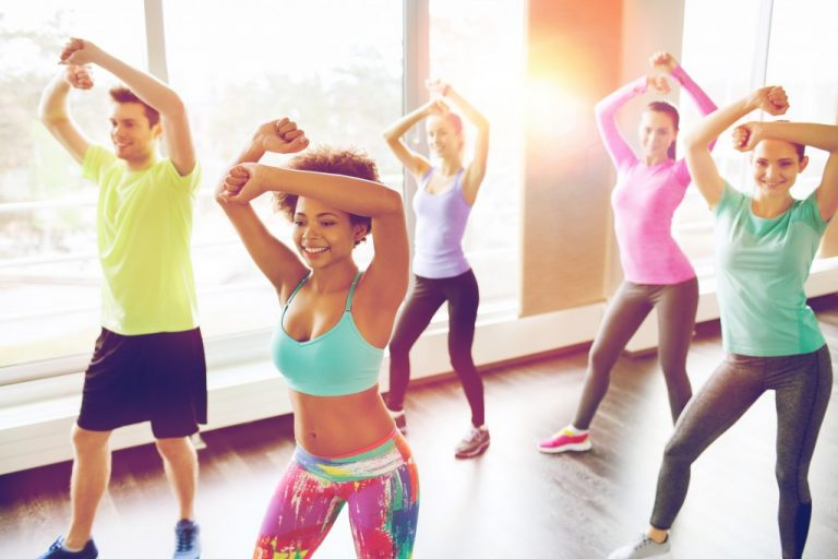 group of smiling people with coach dancing zumba in gym