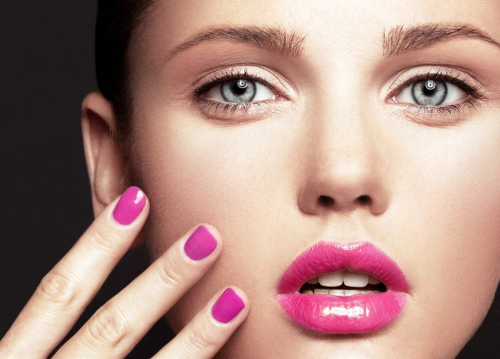 close up beauty shot of woman with pink lip and nails