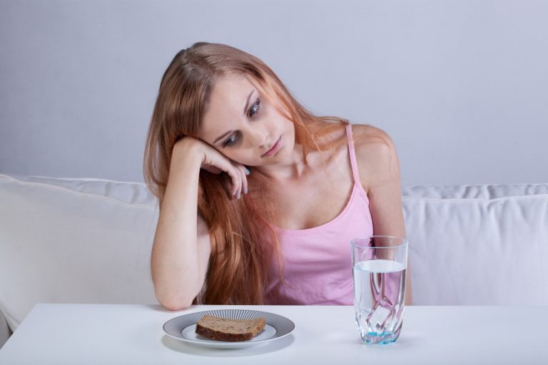 depressed girl starring at the bread on her plate