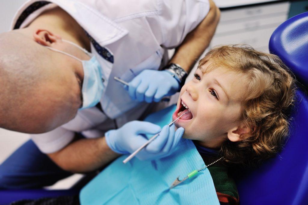 kid having his teeth by a dentist