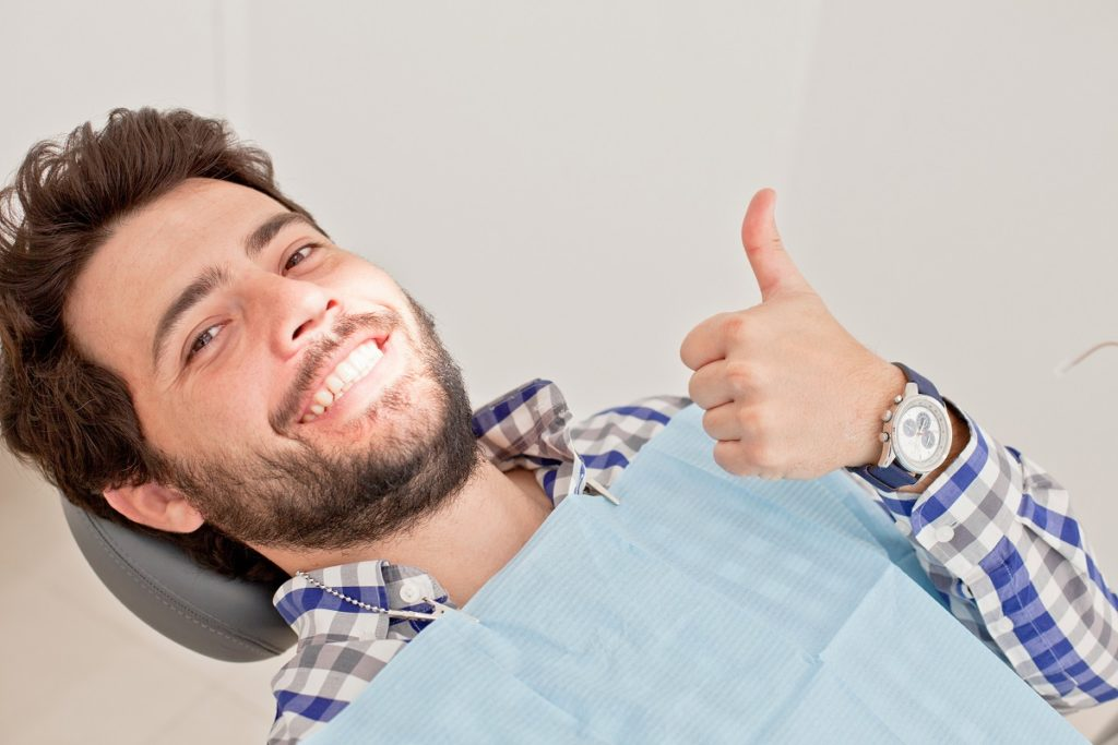 man giving a thumbs up at the dentist