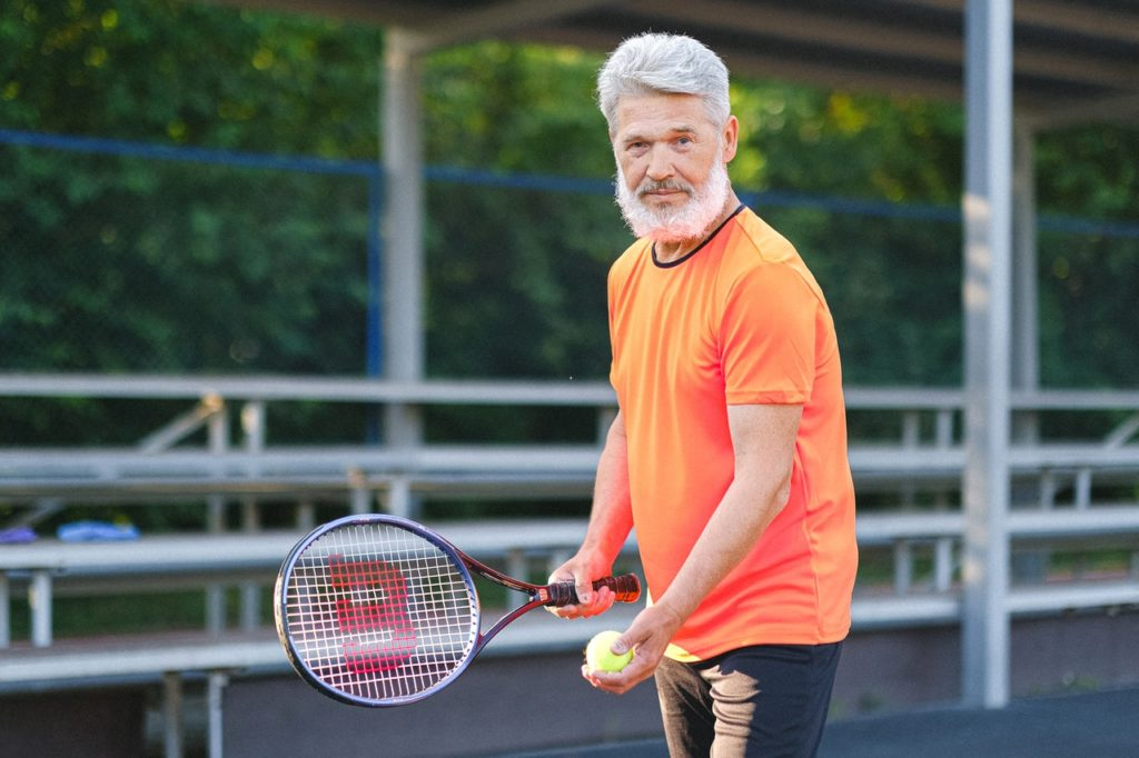 elder man playing tennis