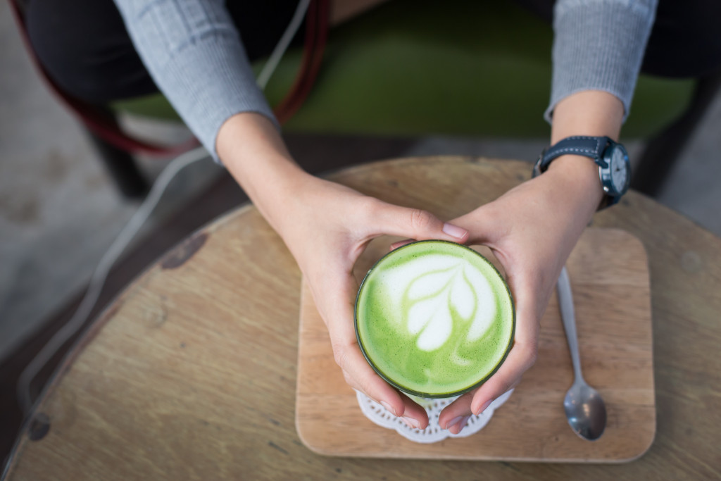 Cup of Matcha Green Tea in woman hand